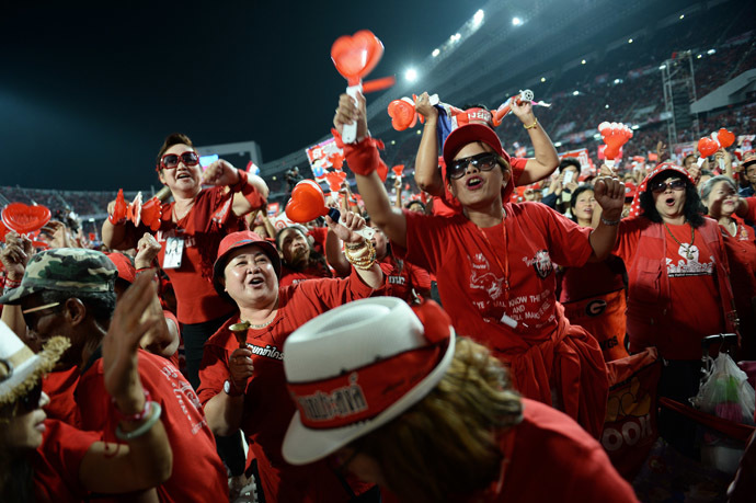 Thai pro-government Red Shirt supporters wave clappers and cheer leaders' speeches during a rally at a stadium in Bangkok on November 30, 2013. (AFP Photo/Christophe Archambault)