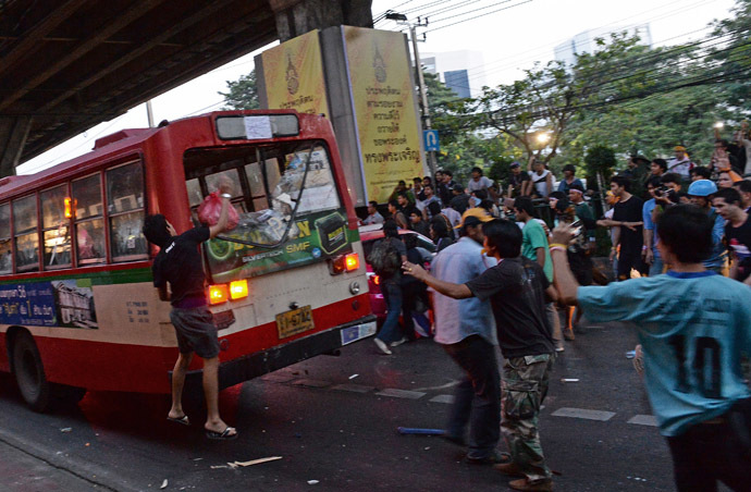 Thai opposition protesters attack a bus carrying pro-government Red Shirt supporters on their way to a rally at a stadium in Bangkok on November 30, 2013.(AFP Photo/Christophe Archambault)