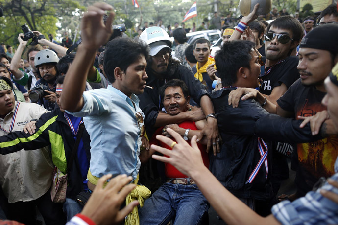 A man is attacked by anti-government protesters near the stadium where pro-government red shirts are gathering in Bangkok November 30, 2013. (Reuters/Damir Sagolj)