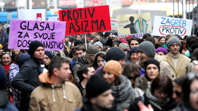 "Croatian gay rights supporters hold signs reading ""Against fascism"" and ""Vote against"" as they gather for a protest outside the parliament building in Saint Marko Square in Zagreb on November 30, 2013.(AFP Photo / STR)"
