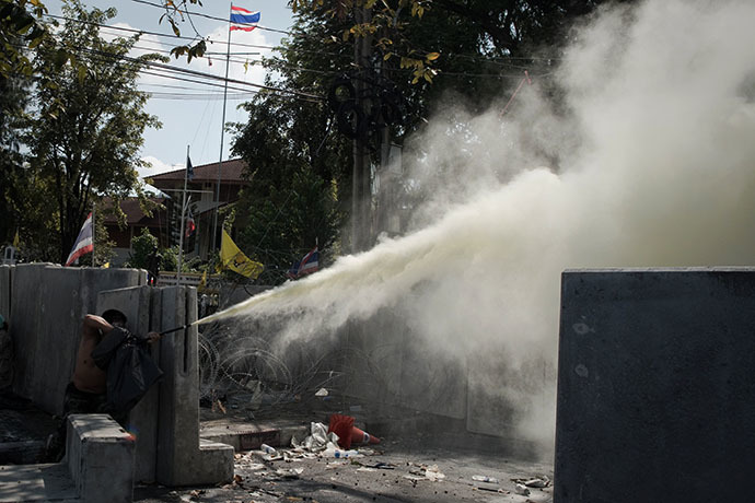 An anti-government protester throw smoke to the police outside Governement House during a demonstration in Bangkok on December 1, 2013. (AFP Photo / Nicolas Asfouri)
