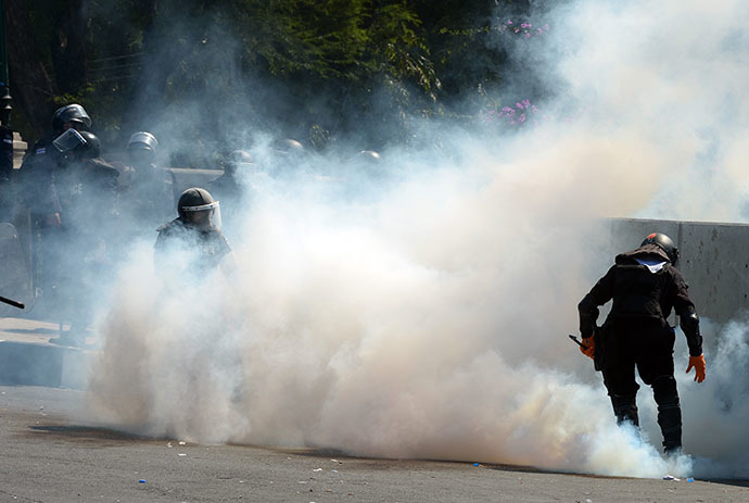 Thai riot policemen collect tear gas from anti-government protesters during demonstration at Governement House during a demonstration in Bangkok on December 1, 2013. (AFP Photo / Pornchai Kittiwongsakul)