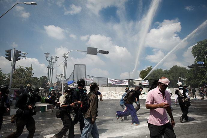 Anti-government protesters and the media run from water canons outside Governement house during a demonstration in Bangkok on December 1, 2013. (AFP Photo / Nicolas Asfouri)