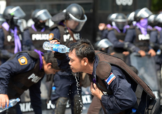 Thai riot policemen clean their faces from tear gas during an anti-government demonstration at Government House in Bangkok on December 1, 2013. (AFP Photo / Pornchai Kittiwongsakul)