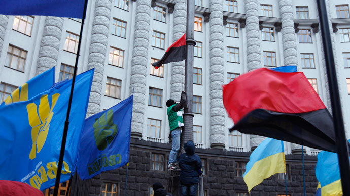 A man attaches a red and black flag, widely used by Ukrainian nationalists, to a lamp post in front of the Ukrainian cabinet of ministers building in the early morning hours during a rally to support EU integration in Kiev December 5, 2013.(Reuters / Vasily Fedosenko)