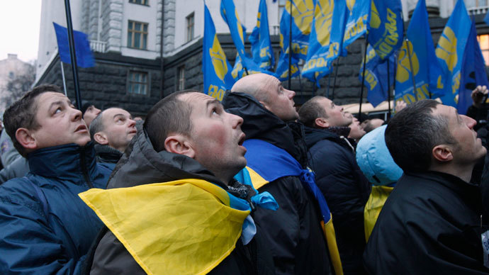 Men look at a flag being attached to a lamp post as they gather in front of the Ukrainian cabinet of ministers building, during a rally to support EU integration in Kiev December 5, 2013.(Reuters / Vasily Fedosenko)