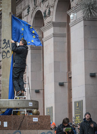 Supporter of Ukraine's European integration hangs a EU flag on a building of city Rada in Kiev.(RIA Novosti / Alexey Kudenko)