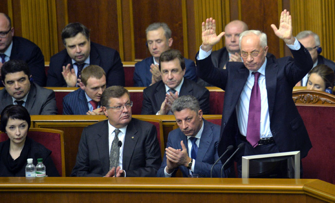 Ukraine's Prime Miister Mykola Azarov greets deputies of the majority after a vote for his resignation at the parliament in Kiev on December 3, 2013. (AFP Photo/Sergei Supinsky)
