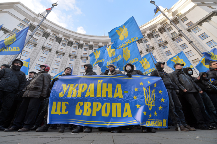 "Protesters hold a placards reading ""Ukraine is Europe"" as they block the Ukrainian Cabinet of the (AFP Photo / Sergei Supinsky)"