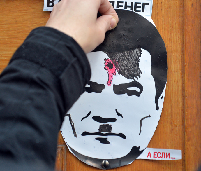 A man attaches a poster with a portrait of the President Viktor Yanukovych depicted as Adolh Hitler with a bullet hole in his head as the protesters block the Ukrainian Cabinet of the Ministers building in Kiev on December 2, 2013. (AFP Photo / Sergei Supinsky)