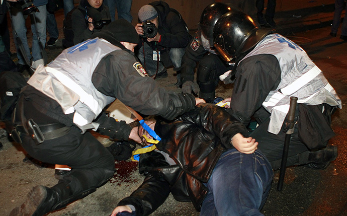 An injured man receives medical help from Interior Ministry members during a rally held by supporters of EU integration in Kiev, December 1, 2013. (Reuters / Gleb Garanich)