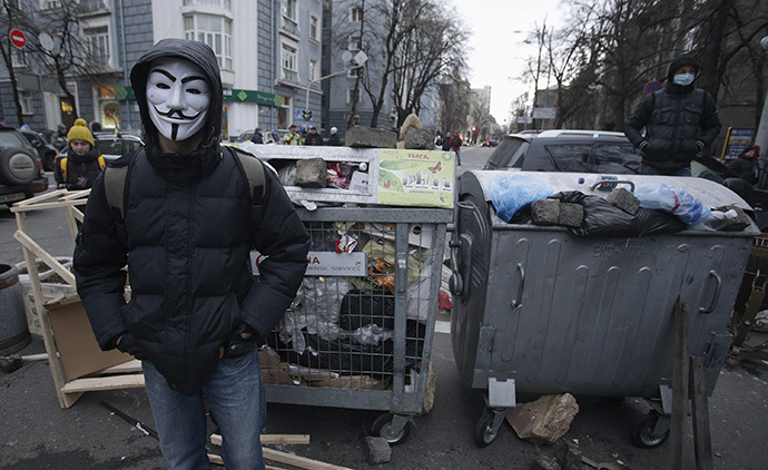 A protester wearing a Guy Fawkes mask stands in front of a barricade near the government building in Kiev December 2, 2013. (Reuters / Stoyan Nenov)