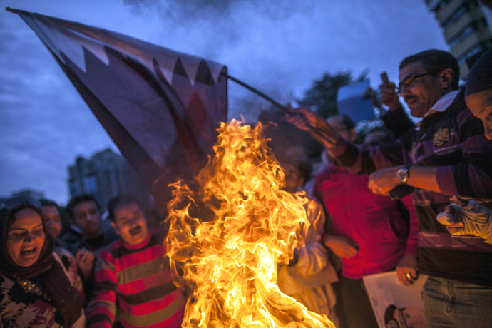 Supporters of Egypt's military chief Abdel Fattah al-Sisi burn a Qatari national flag during a demonstration outside the Qatari embassy in Cairo on November 30, 2013 (AFP Photo)