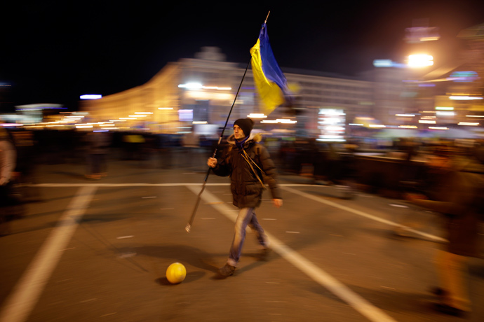 A protester holding a Ukrainian flag plays soccer during a rally at Independence Square in Kiev December 2, 2013. (Reuters / Stoyan Nenov)