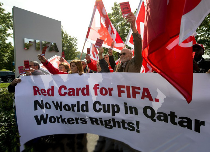 "Members of Building and Wood Workers' International (BWI) and Swiss Unia unions hold a red cards reading ""A red card for FIFA, no World Cup without labour rights"" and a banner reading ""No World Cup in Qatar Workers Rights!"" during a demonstration outside the headquarters of the world's football governing body FIFA in Zurich on October 3, 2013. (AFP Photo / Fabrice Coffrini)"