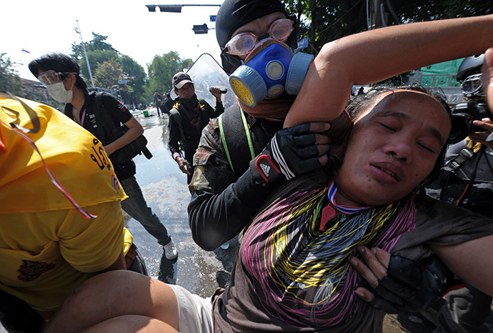 Volunteers carry an injured anti-government protester during a demonstration at the Government House in Bangkok on December 2, 2013. (AFP Photo / Pornchai Kittiwongsakul)
