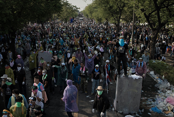 Anti-government protesters stand behind a line of other protesters (not seen) clashing with riot police outside the police headquarters during an ongoing rally in Bangkok on December 2, 2013. (AFP Photo / Nicolas Asfouri)