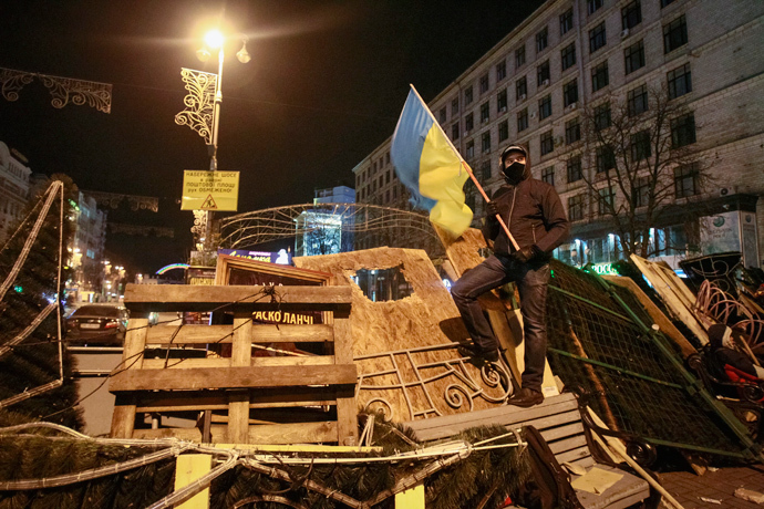 A protester carries a Ukrainian flag as he stands on barricades at Independence Square in Kiev December 2, 2013. (Reuters / Gleb Garanich)