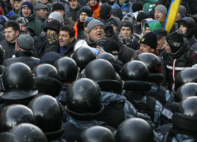 Police stand guard in front of protesters during a demonstration in support of EU integration in front of the Parliament building in Kiev December 3, 2013. (Reuters/Gleb Garanich)