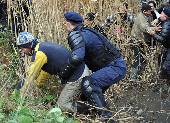 Romanian gendarm scuffle with local people during a protest against shale gas exploition in Pungesti village in Romania on October 16, 2013. (AFP Photo/Adrian Arnautu)