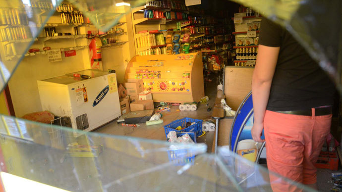 Workers clean a looted a supermarket on December 03, 2013 in Cordoba.(AFP Photo / Irma Montiel)
