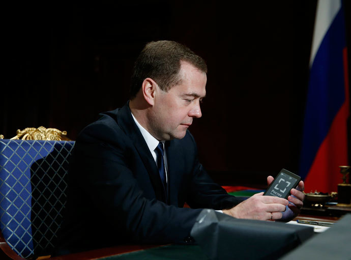 Russia's Prime Minister Dmitry Medvedev holds a YotaPhone smartphone during a meeting with Sergei Chemezov, CEO of Rostec State Corporation, at the Gorki residence outside Moscow, December 4, 2013.(Reuters / Dmitry Astakhov)
