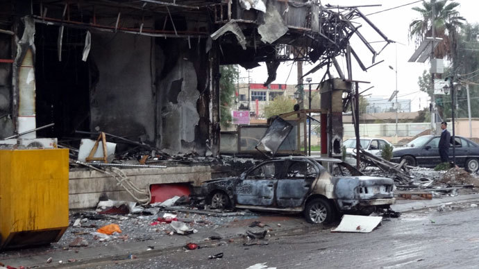 A picture taken on December 5, 2013 shows damages and a burnt vehicle after the mall in the northern Iraqi city of Kirkuk was stormed by security forces to end an hours-long siege that has followed an attack involving a car bomb, gunmen and would-be suicide bombers.(AFP Photo / Marwan Ibrahim)