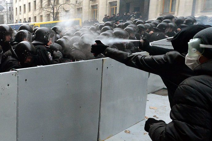 Pro-European Ukrainian demonstrators spray tear gas on police members protecting the presidential adminstration office in Kiev as 100 000 outraged Ukrainians swarmed the city in a call for early elections meant to punish authorities for rejecting a historic EU pact, on December 1, 2013.( AFP Photo / Vasily Maximov)