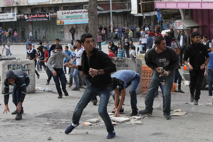 Palestinian stone throwers hurl stones towards Israeli troops during clashes at an Israeli checkpoint in the divided West Bank city of Hebron, near the Jewish settlements of Beit Hadassa and Tal Romeda on September 24, 2013.(AFP Photo / Hazem Bader)