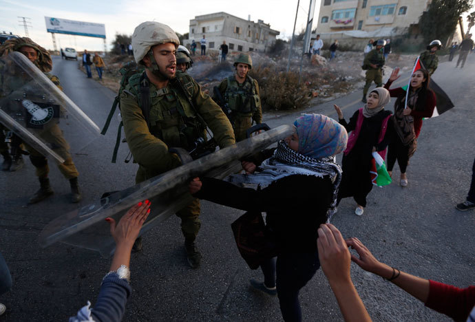 An Israeli soldier scuffles with a Palestinian protester after clashes erupted during a protest against Israel's plan of forced relocation for Bedouin residents in the southern Negev, outside the Beit El settlement near the West Bank city of Ramallah November 30, 2013.(Reuters / Mohamad Torokman )