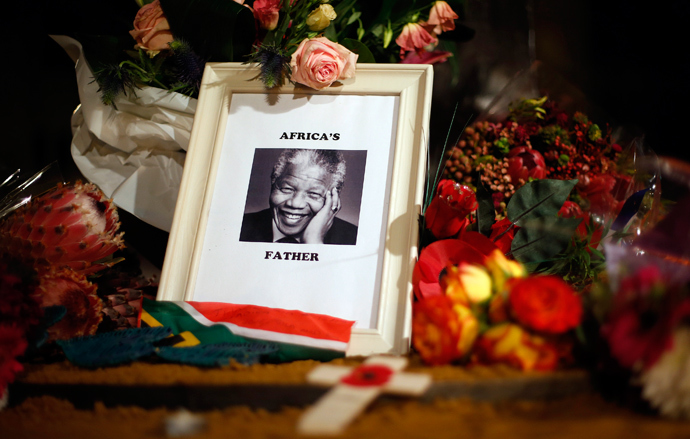 Flowers and tributes are left on the Nelson Mandela statue on Parliament Square in London December 6, 2013. (Reuters / Suzanne Plunkett)