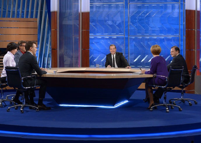 Prime Minister Dmitry Medvedev (center) gives an interview on the round-up of the Government's work in 2013 to federal TV channels at the Ostankino TV Center. (RIA Novosti /Alexander Astafyev)