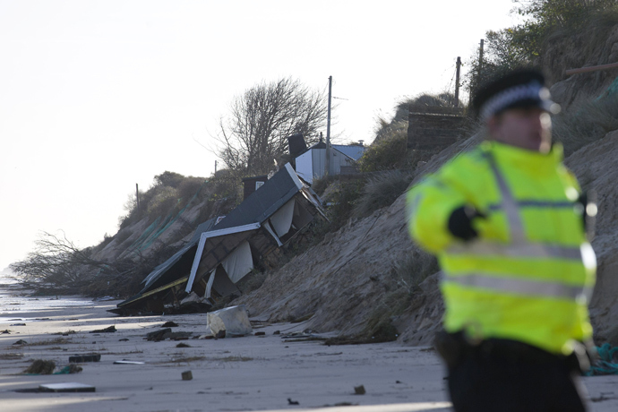 Emergency services personnel stand on the beach near a chalet home that was drawn into th sea during a tidal surge at Hemsby, in the east of England, on December 6, 2013. (AFP Photo / Justin Tallis)