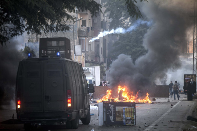 Muslim Brotherhood and ousted president Mohammed Morsi supporters (background) clash with Egyptian riot police during a demonstration in the streets of El Zeitun neighborhood close by al Qubba presidential Palace on December 6, 2013 in Cairo. (AFP Photo/Mahmoud Khaled)