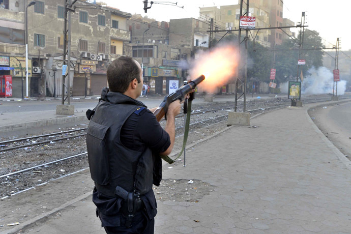 A riot policeman fires tear gas during clashes following a demonstration of Muslim Brotherhood and ousted president Mohammed Morsi supporters on December 6, 2013 in the streets of El Zeitun neighborhood close by al Qubba presidential Palace in Cairo. (AFP Photo/Mahmoud Khaled)
