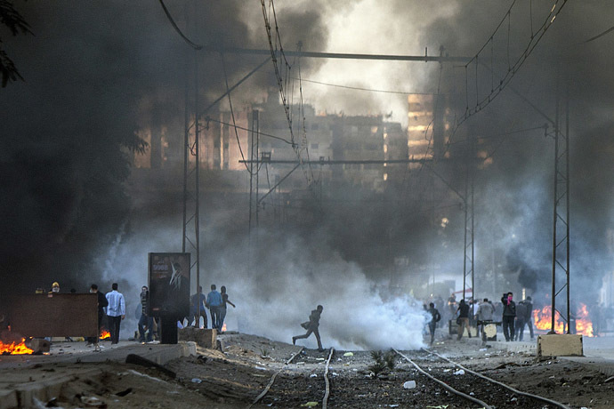 Muslim Brotherhood and ousted president Mohammed Morsi supporters clash with Egyptian riot police during a demonstration in the streets of El Zeitun neighborhood close by al Qubba presidential Palace on December 6, 2013 in Cairo. (AFP Photo/Mahmoud Khaled)