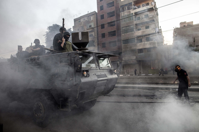 Egyptian security forces patrol on an armoured vehicle during clashes following a demonstration of Muslim Brotherhood and ousted president Mohammed Morsi supporters on December 6, 2013 in the streets of El Zeitun neighborhood close by al Qubba presidential Palace in Cairo. (AFP Photo/Mahmoud Khaled)
