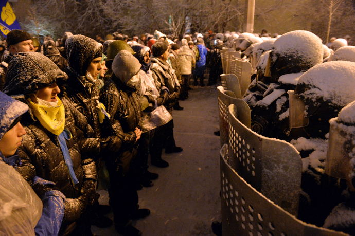 Pro-EU Ukrainian protesters stand opposite riot policemen securing the area outside the presidential office in Kiev on December 9, 2013 (AFP Photo / Sergey Supinsky)