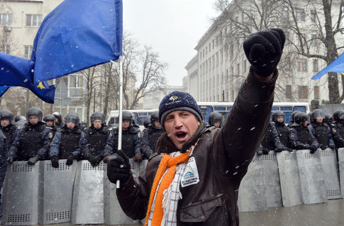 A protester with holding an EU flag shouts slogans in front of riot police during a picket held outside the presidential office in Kiev on December 7, 2013.(AFP Photo / Sergei Supinsky)