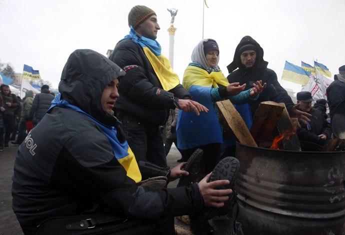 Protesters warm themselves at the camp of the opposition on Maiden (Independence) Square in Kiev on a frosty day in Kiev on December 10, 2013. (AFP Photo / Yuriy Kirnichny)