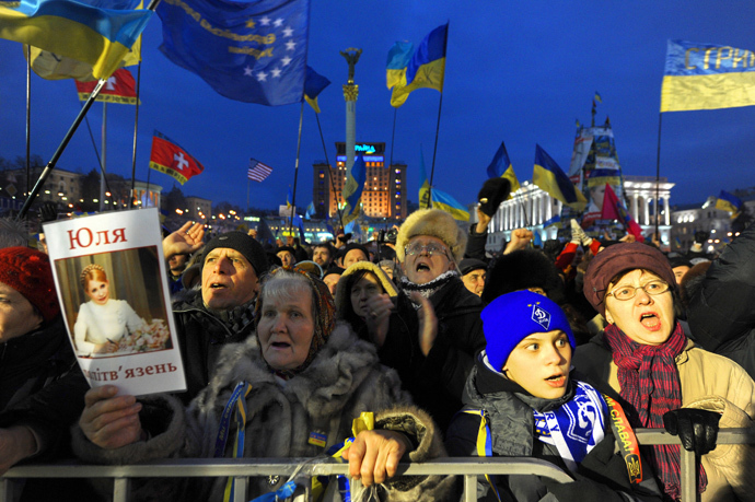 People shout slogans and wave Ukrainian and European Union flags as a woman holds a picture of jailed former Prime Minister Yulia Tymoshenko during a mass rally on Independence Square in Kiev, on December 15, 2013. (AFP Photo / Viktor Drachev)