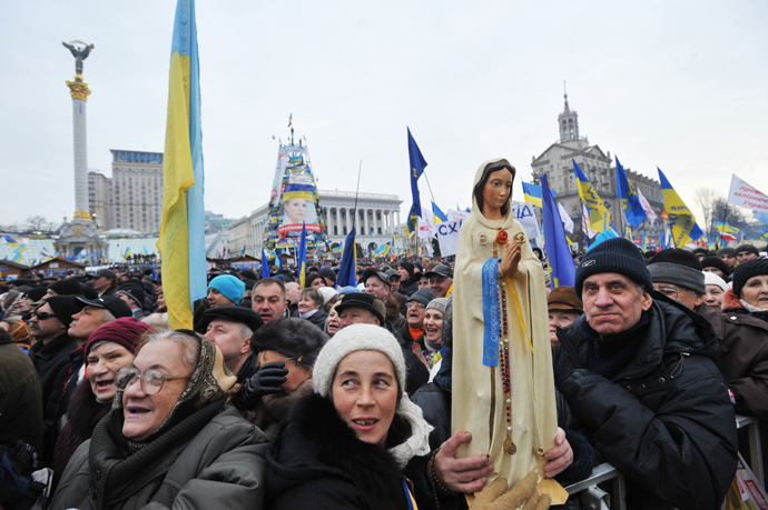 A protestor holds a statue of Virgin Mary during a mass rally of the opposition Independence Square in Kiev on December 15, 2013. (AFP Photo / Genya Savilov)