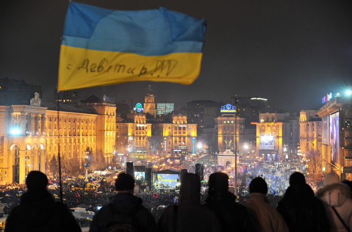 Protesters fly a Ukrainian flag above Independence Square in central Kiev as people gather for an opposition rally on December 17, 2013 (AFP Photo / Genya Savilov)