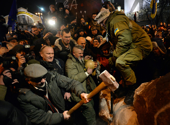 "A protester breaks apart a statue of Lenin at a monument in his honor after it was pulled down during a mass rally called ""The March of a Million"" in Kiev's Independence Square on December 8, 2013. (AFP Photo / Vasily Maximov)"