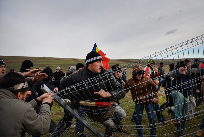 Romanian protesters tear down the fence of the exploring perimeter of US energy giant Chevron in Pungesti, Romania on December 7, 2013. (AFP Photo / Daniel Mihailescu)