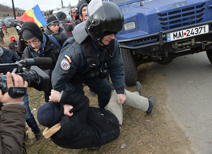 A Romanian protester is lifted by a Romanian gendarme after protesters teared down the fence of the exploring perimeter of US energy giant Chevron in Pungesti, Romania on December 7, 2013. (AFP Photo / Daniel Mihailescu)