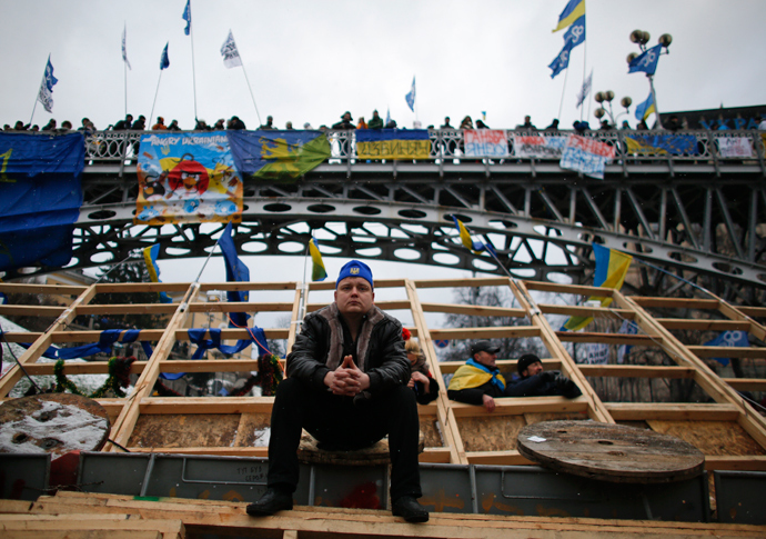 A man sits on a barricade during a rally organized by supporters of EU integration in central Kiev, December 8, 2013 (Reuters / Stoyan Nenov)