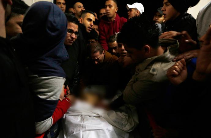Palestinians look at the body of Wajih Majdi Al-Ramahy, 15, in Ramallah hospital December 7, 2013 (Reuters / Mohamad Torokman)