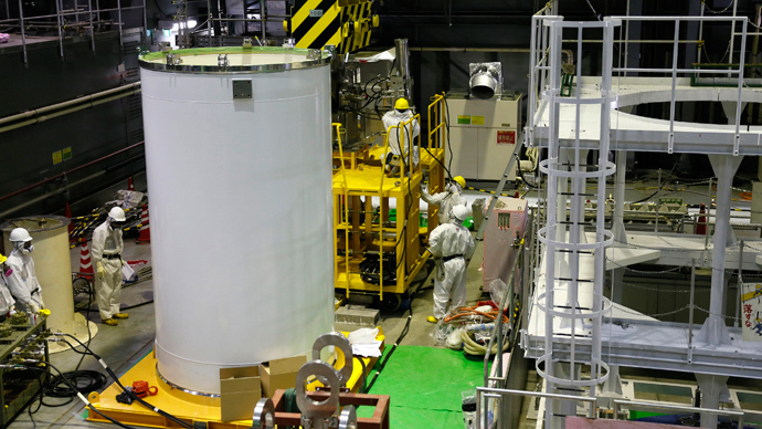 Workers check a transport container and a crane in preparation for the removal of spent nuclear fuel from the spent fuel pool inside the No.4 reactor building at the Tokyo Electric Power Corp's (TEPCO) tsunami-crippled Fukushima Daiichi nuclear power plant, in Fukushima  (Reuters / Kimimasa Mayama / Pool)