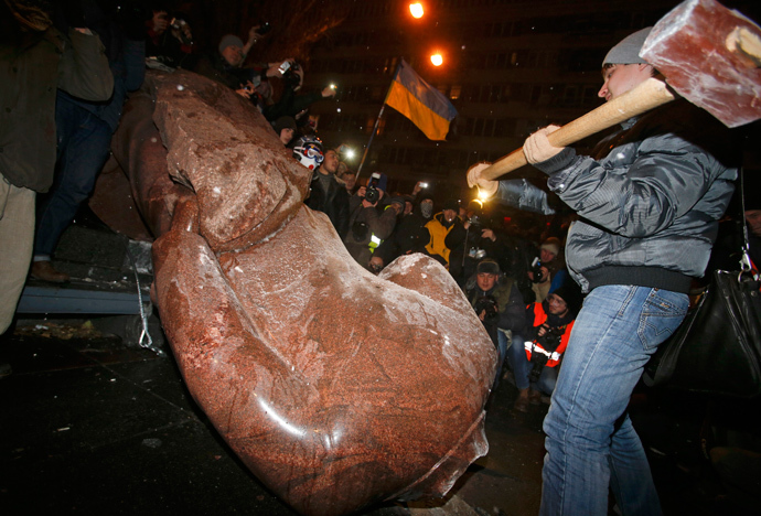 A man holds a sledgehammer as he smashes a statue of Soviet state founder Vladimir Lenin, which was toppled by protesters during a rally organized by supporters of EU integration in Kiev, December 8, 2013. (Reuters / Stoyan Nenov)